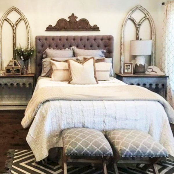 picture of bed with two arches leaning on nightstands and architectural salvage over headboard.