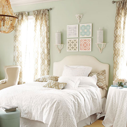 picture of bed with four prints hanging above it.