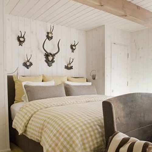 picture of bed with 6 pairs of antlers hanging above it.