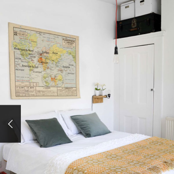 picture of bed with vintage map hanging above it.