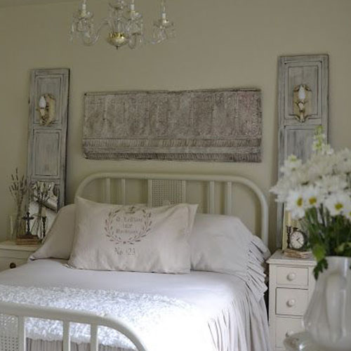 picture of bed with pressed tins hanging above and next to it.