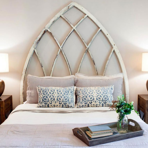 picture of bed with large cathedral arch used as headboard.