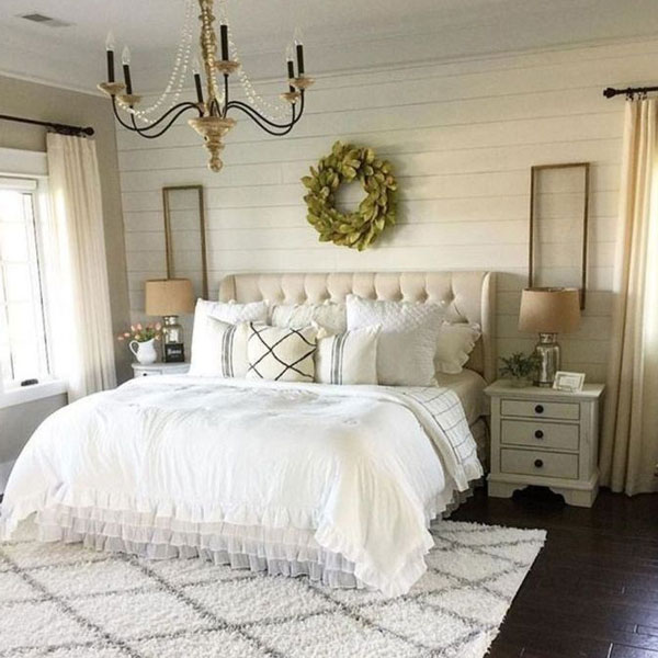 picture of bed with single wreath and two small window screens hanging above it.