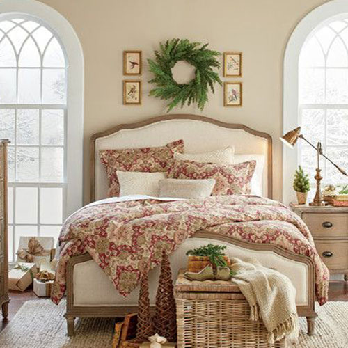 picture of bed with wreath and four small prints hanging above it.