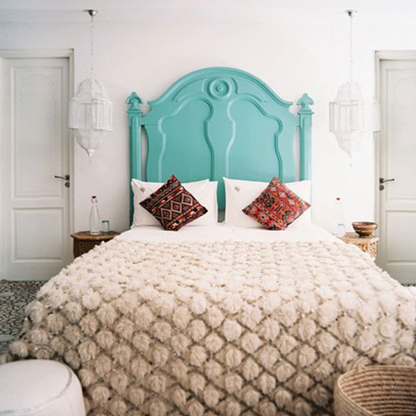 picture of bed with ornate teal painted headboard.